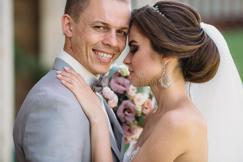 The groom in a gray suit, white shirt, smiles widely in the arms of the bride. The newlyweds embrace on a wedding day. Bride with a beautiful hairstyle in a stock photo