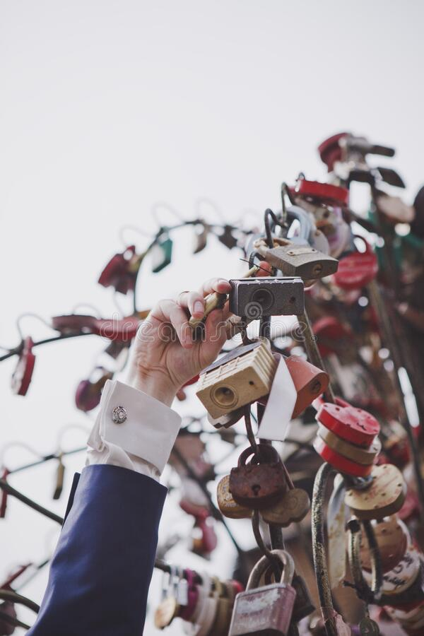 The groom hangs the wedding lock. stock photography