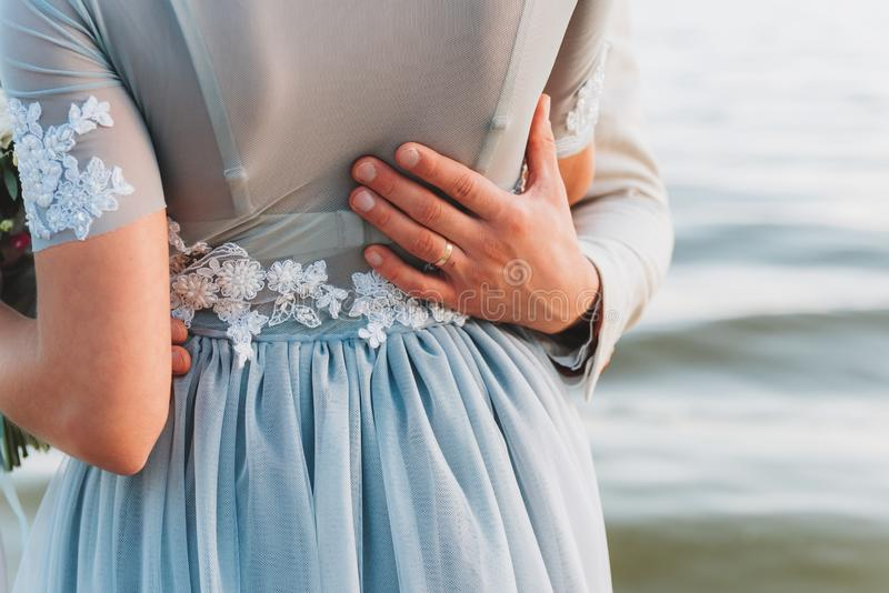 Groom having his hand on his bride`s waist, standing on a beach stock image