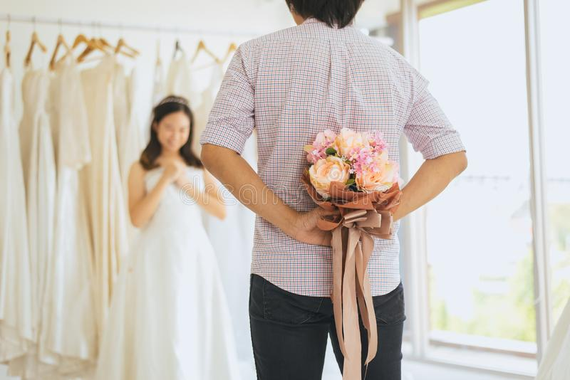 Groom hiding flower behind back in order to surprise bride,Woman positive emotion and face astonished happy and smling royalty free stock photos