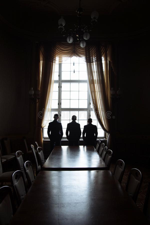 Groom and his best men are standing in the old palace hall near the window. Black and white photo of friends in the royal design stock images