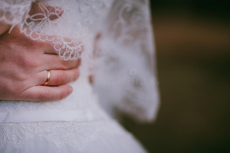 Groom hold bride outdoor. Hand wearing wedding ring on white dress. Close up stock photo