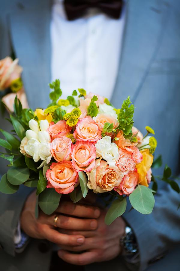 Groom hold wedding bouquet in his hand stock image