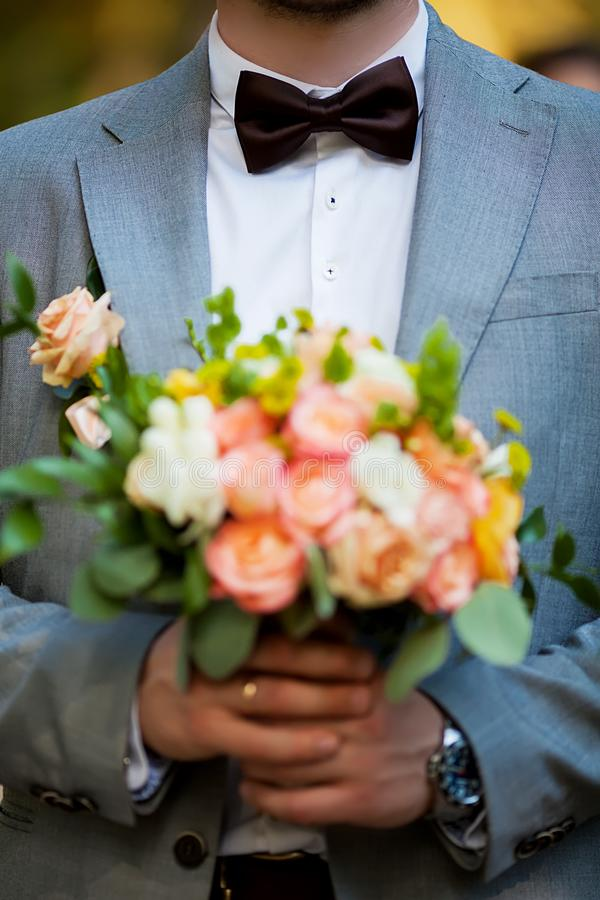Groom hold wedding bouquet in his hand royalty free stock photo