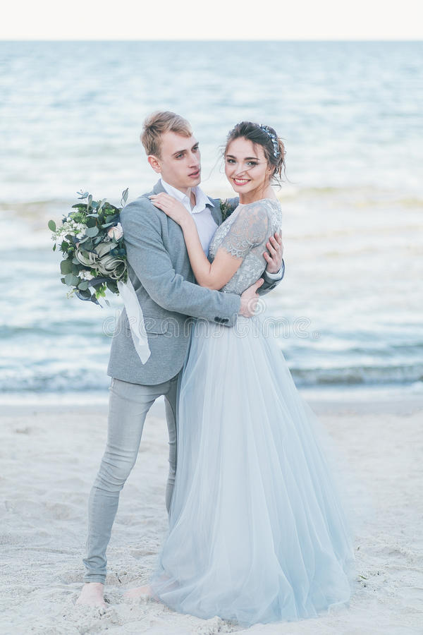 Groom holding in arms bride by the sea royalty free stock photography