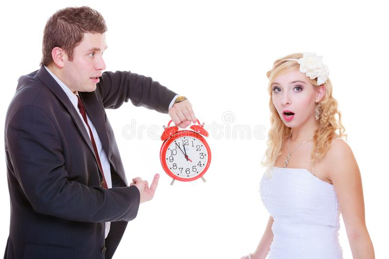 Groom holding big red clock yelling and bride. Wedding, waiting for celebration and proposal, negative bad relationship concept. Groom holding bid red clock royalty free stock photo