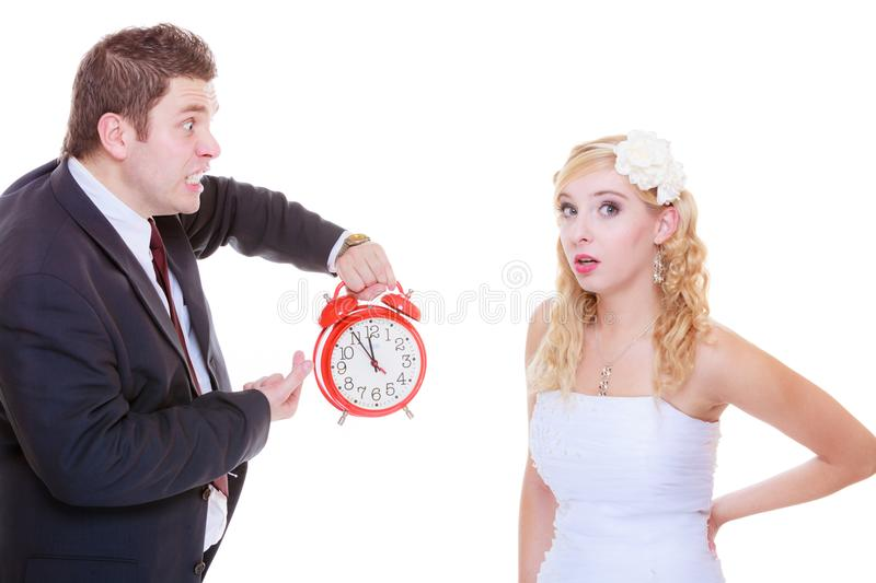 Groom holding big red clock yelling and bride. Wedding, waiting for celebration and proposal, negative bad relationship concept. Groom holding bid red clock royalty free stock image