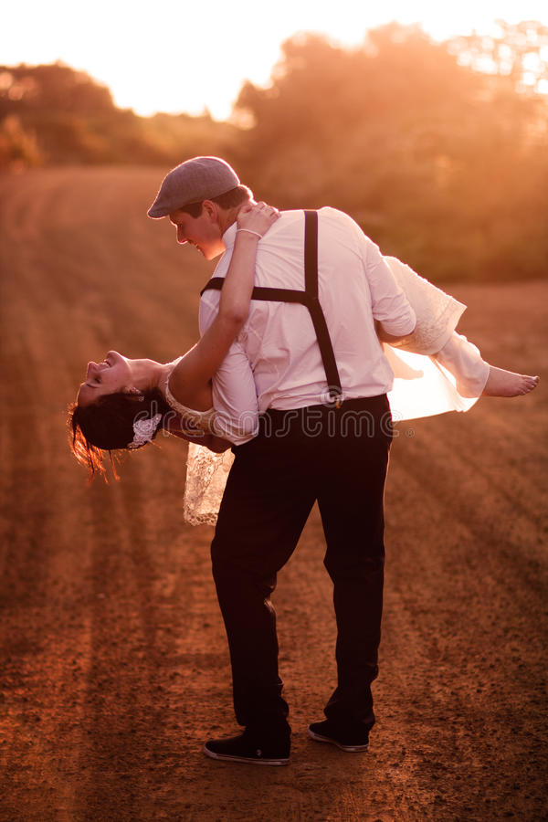 Bride and groom at sunset. Groom holding his bride and dipping her along a country road royalty free stock image
