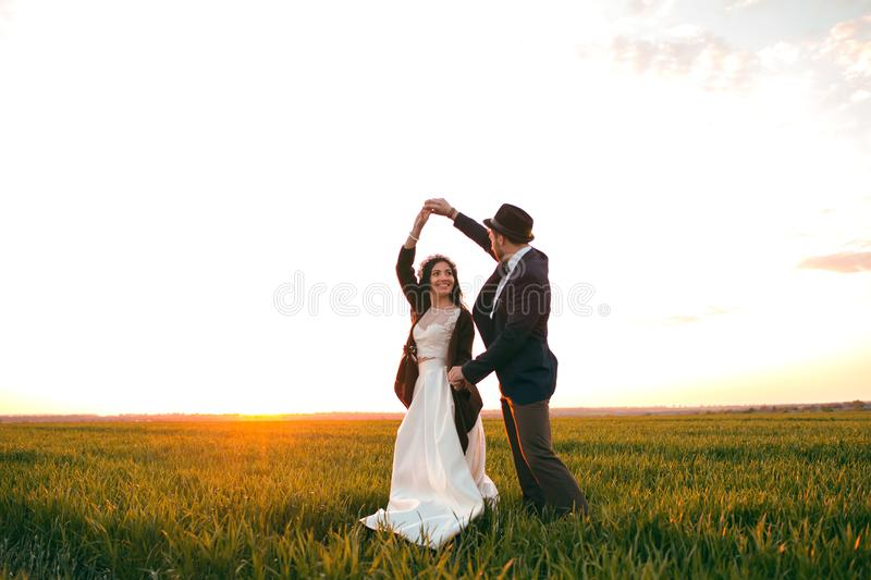 Groom holding bride in dance pose on wedding dayThe groom holds the bride in a dance pose on the wedding day, a young couple royalty free stock image
