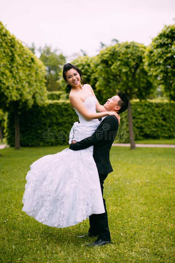 Groom holding bride. In his arms royalty free stock image