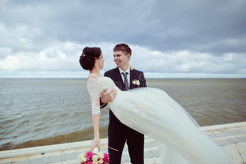 Groom holding bride stock photography