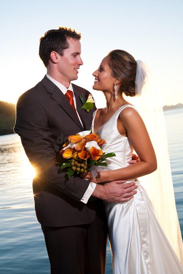 Groom holding bride at sunset with sunburst royalty free stock image