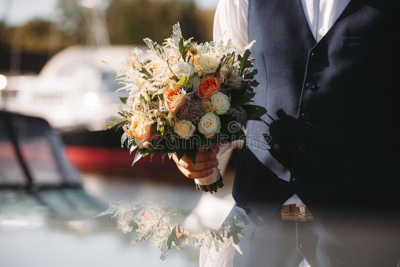 Groom holding in hands delicate, expensive, trendy bridal wedding bouquet of flowers. Attached to the black suit royalty free stock photos