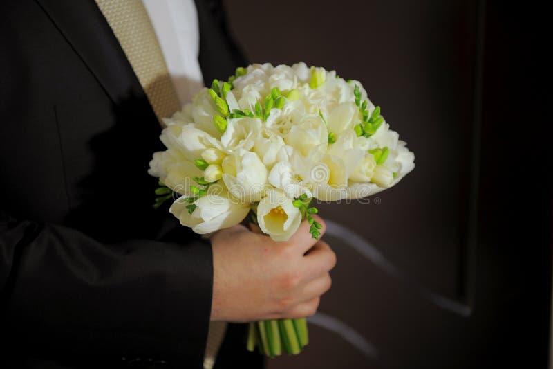 Groom holding wedding bouquet royalty free stock photo
