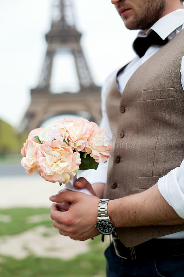 Groom holding a wedding bouquet of white roses. stock photo