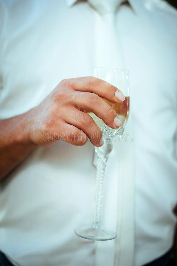 Groom holding wedding champagne glasses. closeup stock photography