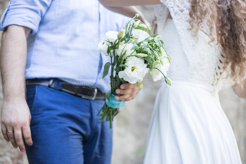 Groom holds bouquet, bride straightens shirt. Newlyweds on background of white flowers royalty free stock photo