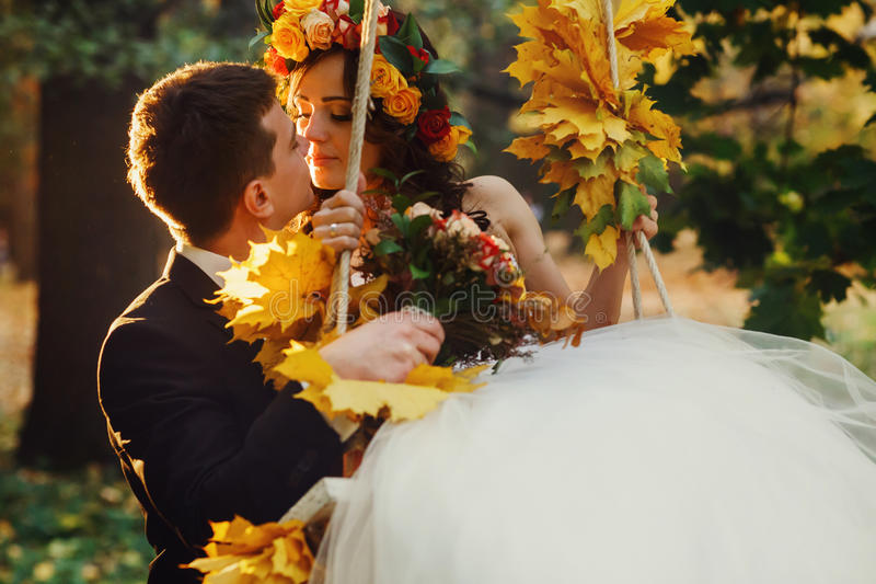 Groom holds a bride in a swing decorated with yellow fallen leaves royalty free stock photography