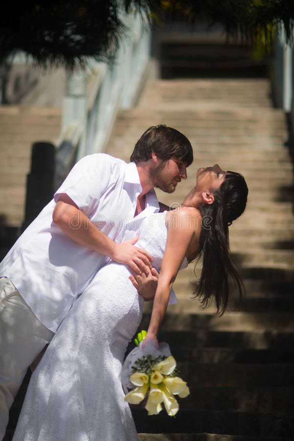 Groom holds the bride by the waist and kisses her passionately on the stone steps stock images