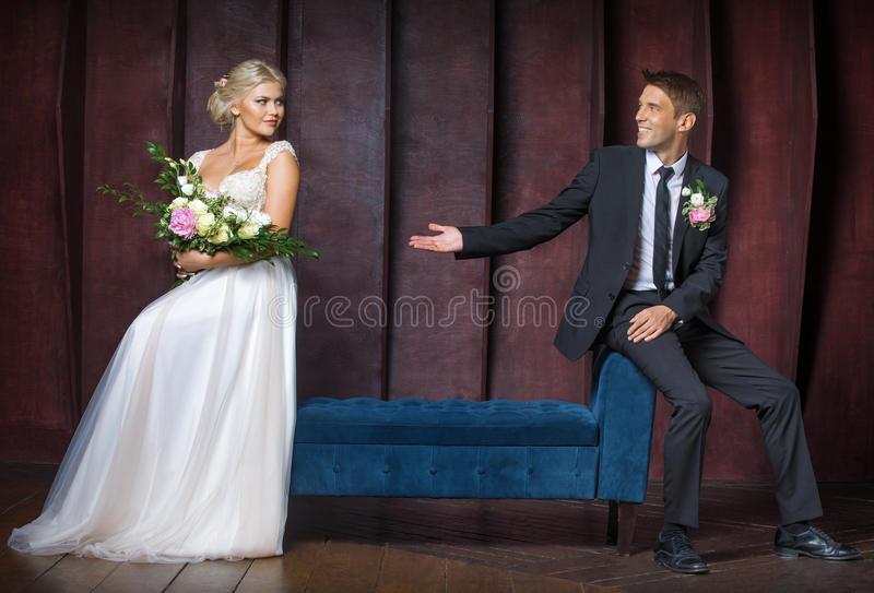 Groom holds the hand of the bride stock photography