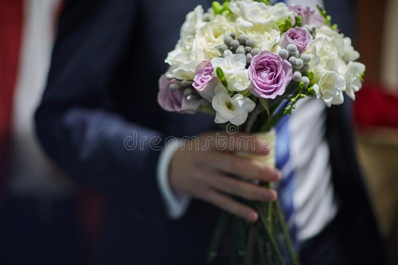 The groom holds in his hands a beautiful bouquet of the bride royalty free stock image