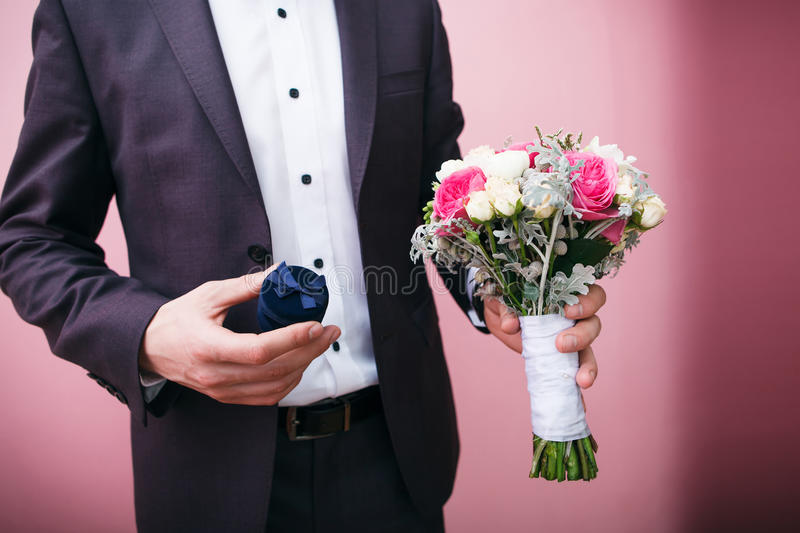 Groom holds wedding bouquet and velvet gift box royalty free stock photos