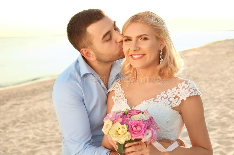 Groom hugging and kissing bride on beach royalty free stock image