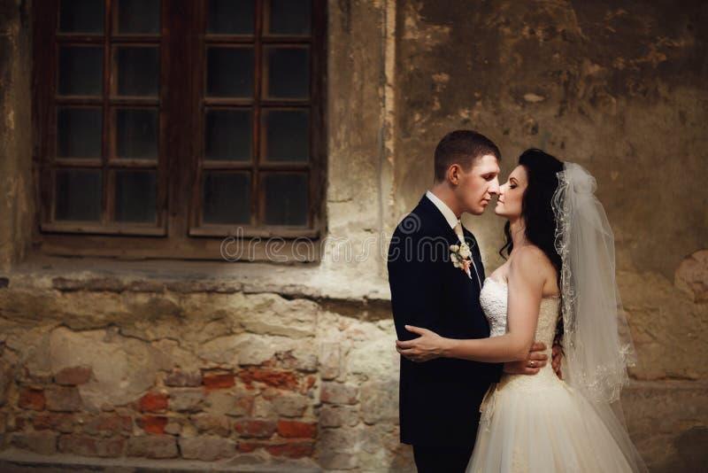 Groom huging kissing beautiful bride near wall outdoors Lviv royalty free stock images