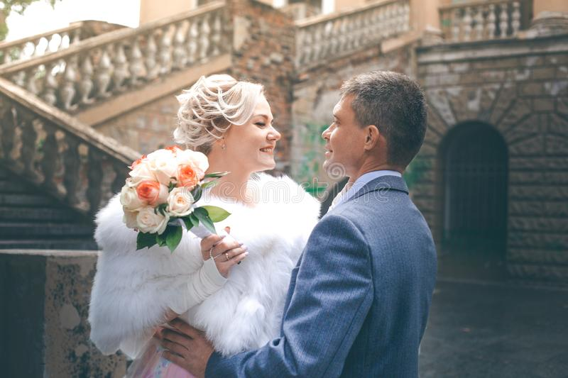Groom hugs the bride in a white dress that holds a bouquet. Of white and red roses against the background of the stairs in the park stock photography