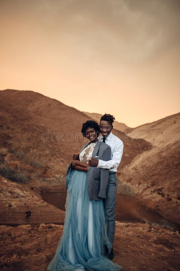 Groom hugs his bride dressed in his jacket in canyon at sunset. Black groom hugs his bride dressed in his jacket in canyon against beautiful landscape at sunset royalty free stock photography