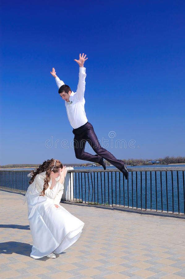 The groom jumps on the bride stock photo