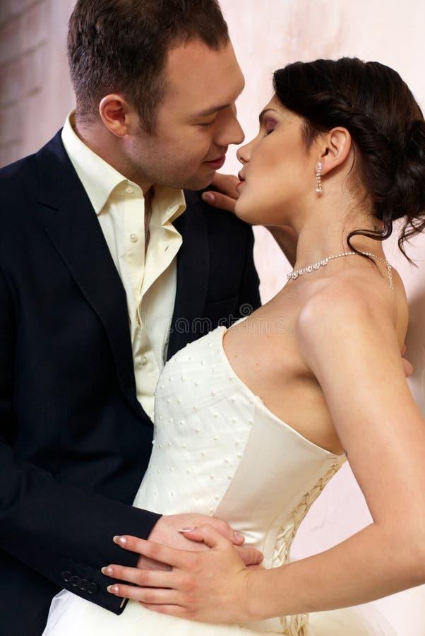 Groom kisses bride in empty room royalty free stock photos