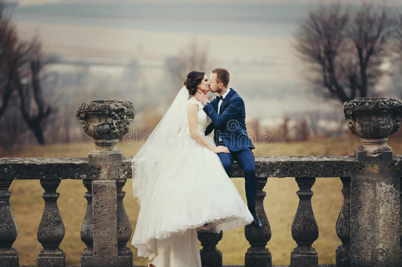 Groom kisses a bride sitting with her on the balcony with a great landscape behind them stock images
