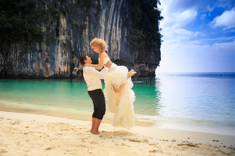 Groom lifts blonde curly bride in fluffy dress holds on beach. Groom lifts blonde curly bride in fluffy wedding dress holds over body on edge of beach against stock photography