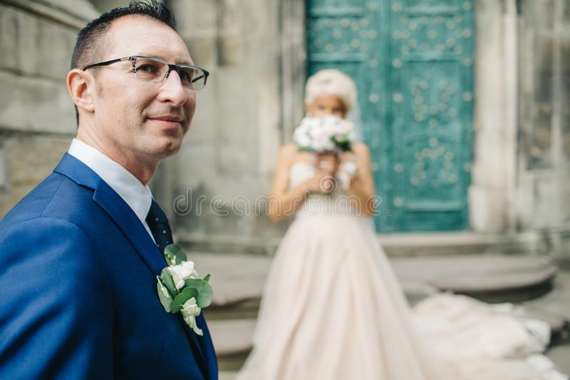 Young couple man and woman gently and passionately embracing eac. Groom looks over his shoulder while bride stands behind him stock photography