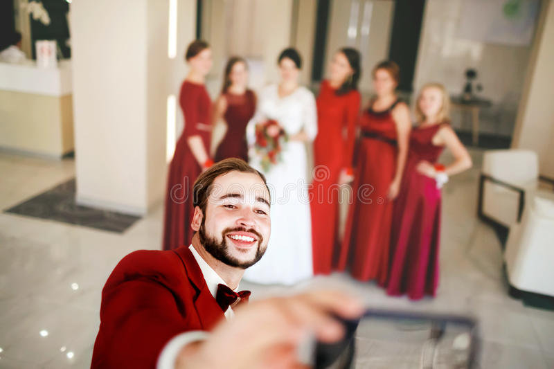 Groom makes selfie on background of bride with bridesmaids group photo. Groom makes selfie on the background of a bride with the bridesmaids group photo. Red royalty free stock images