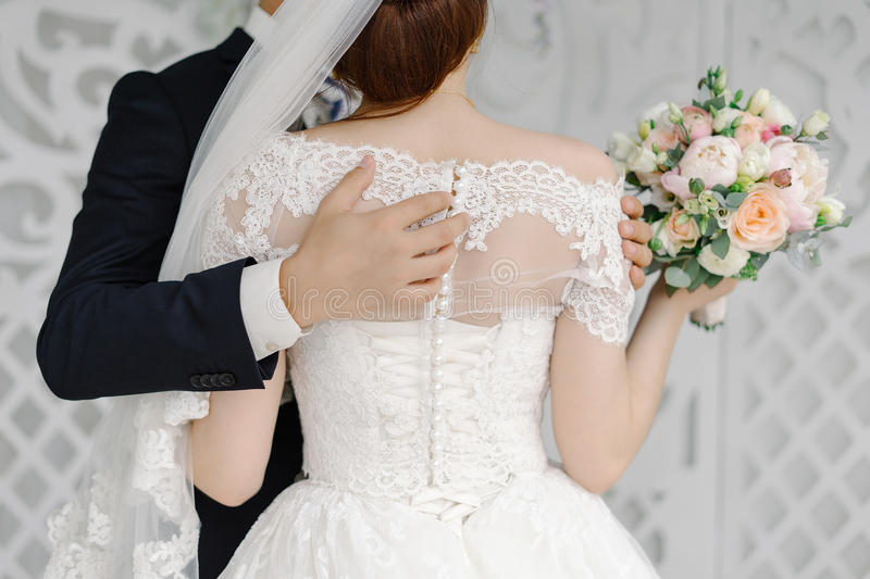 Groom passionately hugs beautiful bride the back view stock photo