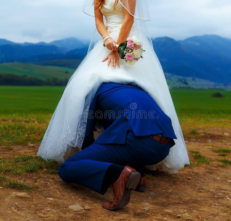 Groom peeking under his bride dress - funny wedding concept. royalty free stock photo