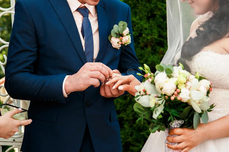 The groom places the wedding ring on the bride`s finger stock photos