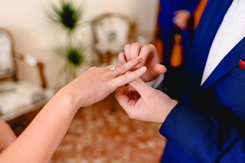 Groom placing ring of request to his fiancee.  stock photography