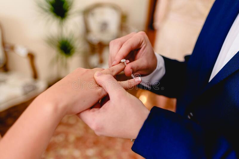 Groom placing ring of request to his fiancee.  stock photos