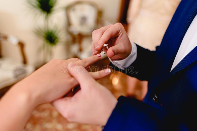 Groom placing ring of request to his fiancee.  stock photo