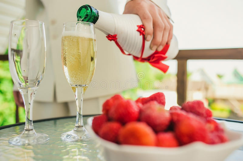 Groom pouring champagne into a glass in the open stock photos