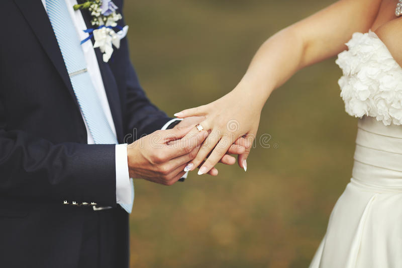 Groom put a wedding ring on finger of his lovely bride stock photography
