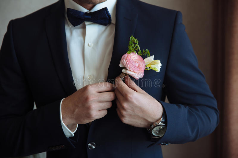 The groom puts on a boutonniere on a wedding day on a jacket royalty free stock images