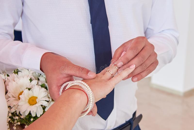 The groom puts the bride ring on the day of their wedding. The groom puts the bride ring on their wedding day stock photo