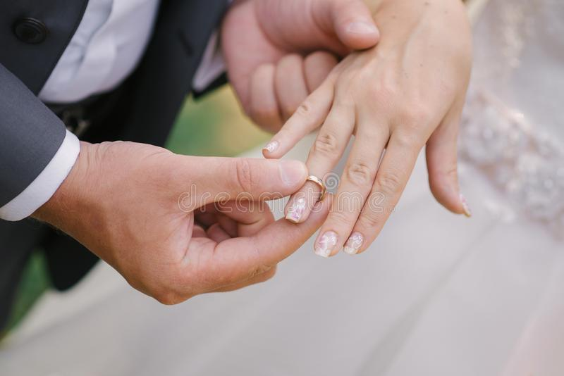 The groom puts on a finger ring wedding bride. Wedding registration of marriage. Close-up of the hands of the couple royalty free stock photos