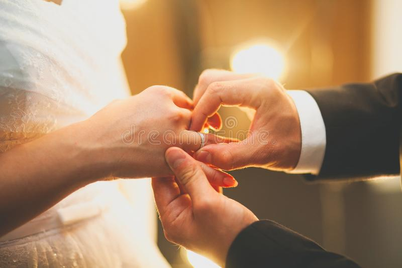 The groom puts the ring on the bride`s hand. Hands of the newlyweds on the wedding day, close-up. The exchange of rings during th. E marriage stock photo