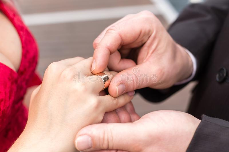Groom puts a wide wedding ring on the finger of Bride, dressed in a sexy red dress stock images