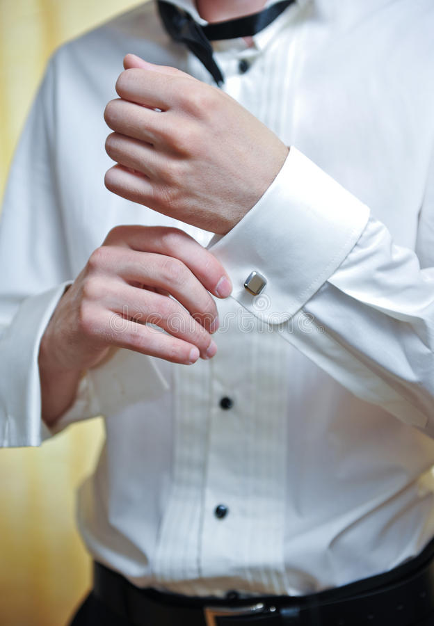A groom putting on cuff-links as he gets dressed. In formal wear stock image